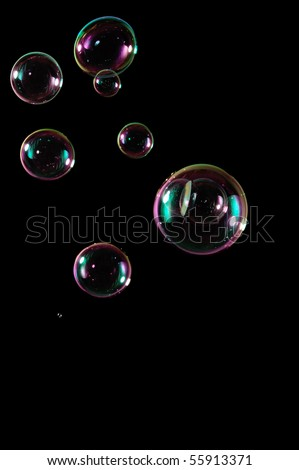 A bunch of bubbles isolated perfectly on a pitch black background. - stock photo
