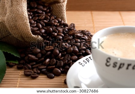 A bunch of coffee beans, falling out of a sack and a cup of fresh coffee on a wooden background - stock photo