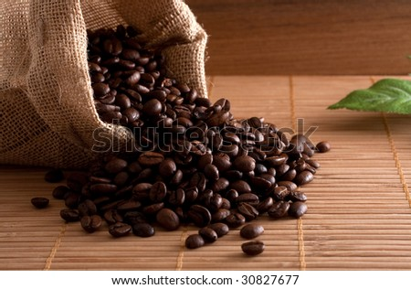 A bunch of coffee beans, falling out of a sack on a wooden background