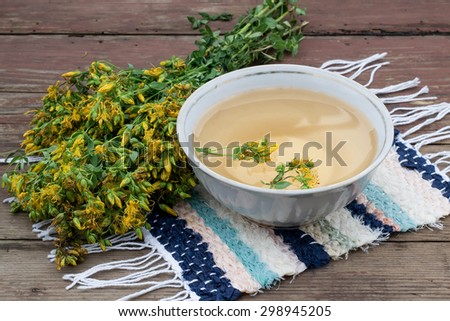 A bunch of flowers St. John's wort (Hypericum perforatum) and freshly brewed tea on a hand-woven rug and an old wooden table - stock photo