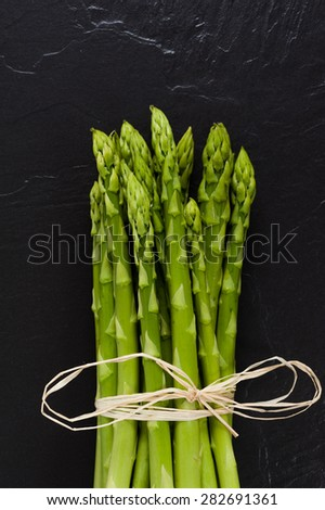 A bunch of fresh green Asparagus on Slate. Close-up. - stock photo