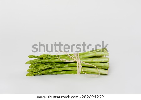 A bunch of fresh green Asparagus on white. - stock photo