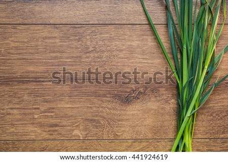 A bunch of fresh spring green grass on a wooden background. Old wooden texture with terrestrial plants. Land plants. Plant with green stems and low, components for  preparation salad. Vegetarian food - stock photo