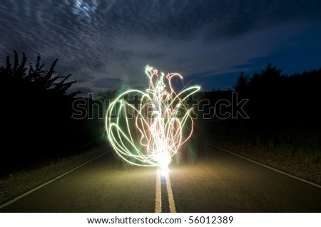 A bunch of glowing abstract sparkler background image of sparks flying around on the street at night - stock photo