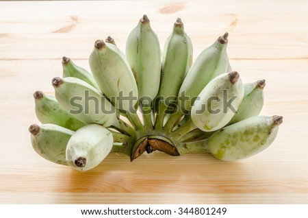 A bunch of green banana on the wooden background - stock photo