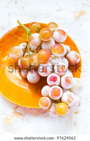 A bunch of icy frosted grapes - muscat variety.  Top view of grapes on a vintage orange plate. - stock photo