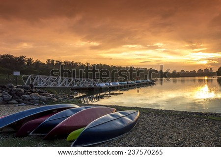 A bunch of kayaks stranded with a orange sunset background - stock photo