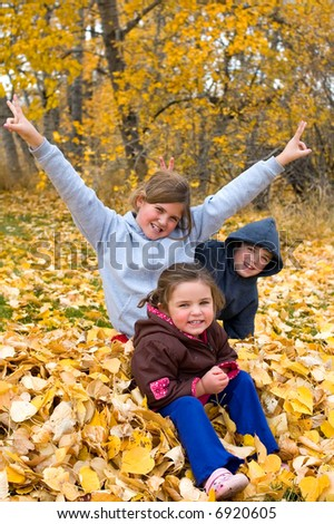 A bunch of kids having fun in some leaves. - stock photo