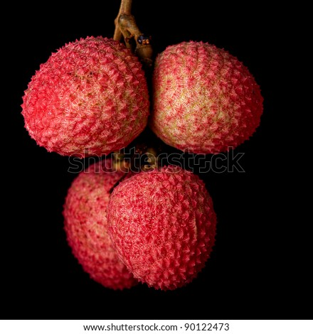 A bunch of lychees against a black background - stock photo