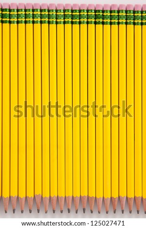 A bunch of number 2 pencils, laid out in a row, on a white background. - stock photo