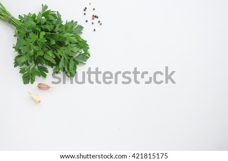 a bunch of parsley, garlic and pepper on a white wooden background - stock photo