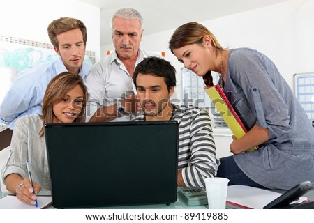 a bunch of people gathered behind a laptop - stock photo