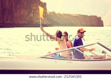 a bunch of people on a boat with one waving a flag indicating a water skier in the water toned with a retro vintage instagram filter effect - stock photo