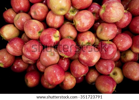 A bunch of Pink lady Apples on a black background