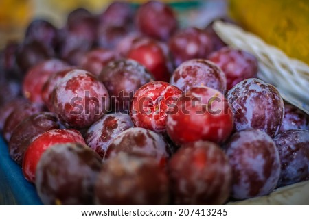 A bunch of plums in a basket at a local farmer's market on Madeira - stock photo