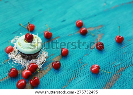 A bunch of red ripe cherries composition with a chocolate muffin and white cream topping placed over white shredded ripped paper over blue textured vintage wood - stock photo