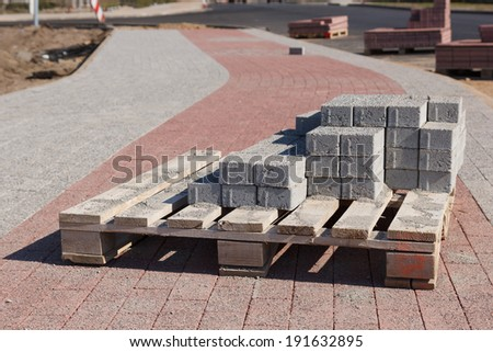 A bunch of road construction bricks placed on a wooden supporter - stock photo