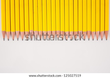 A bunch of sharped, yellow, number 2 pencils, laid out in a row, on a white background. - stock photo