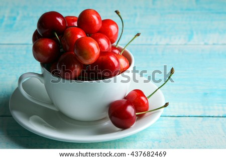 a bunch of sweet cherries and poured in a Cup on blue wooden background - stock photo