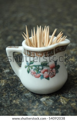 A bunch of toothpicks contained in a miniature tea glass resting on a black counter top with shallow depth of field - stock photo