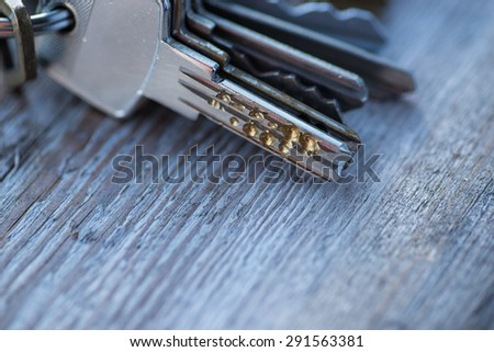 A bunch of vintage keys on the wooden table - stock photo