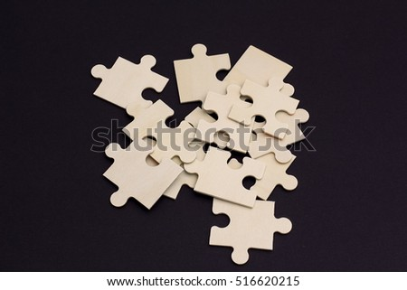 a bunch of wooden puzzle pieces on a black background