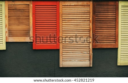 A bunch of wooden window shutters pattern on grey wall. Restaurant cafe warehouse decor. Naked worn wooden and plain painted shutters. Hipster loft wallpaper.  - stock photo