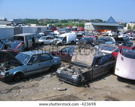 A bunch of wrecked cars at a scrapyard