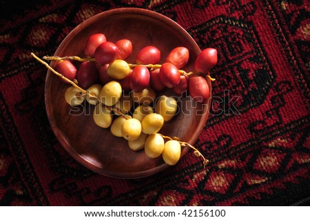 A bunch of yellow and red raw date in a wooden plate. - stock photo