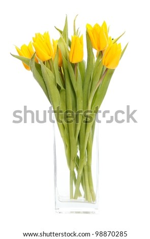 A bunch of yellow tulips in a vase of glass