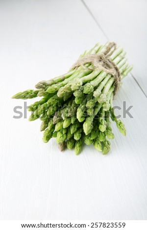 A bundle of fresh green asparagus on rustic white wooden table. - stock photo