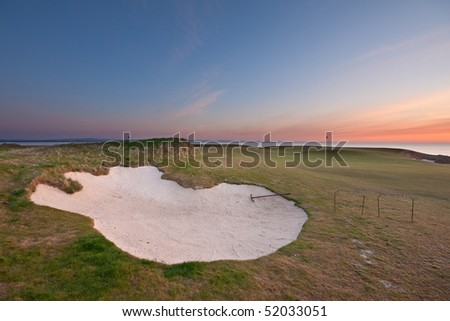 A bunker on the Castle Course links in St Andrews, Scotland, at sunrise. Colourful sky and sea in the background.