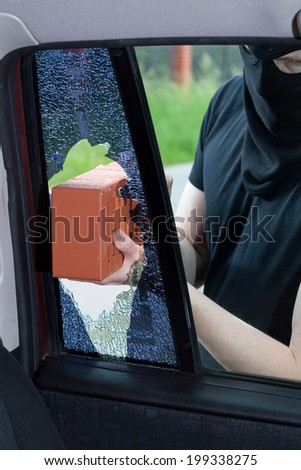 A burglar breaks a window with a brick in the car - stock photo