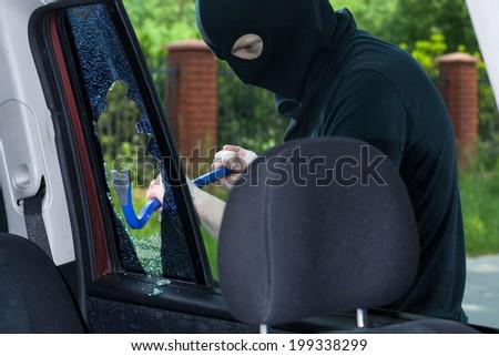 A burglar breaks a window with a crowbar in the car - stock photo