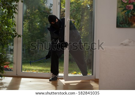 A burglar entering a house through a balcony window - stock photo