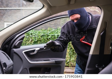 A burglar in action to rob something out of a car - stock photo