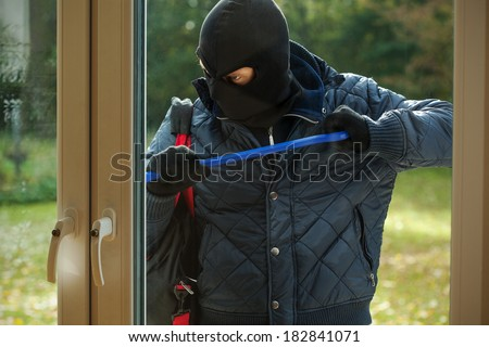 A burglar striving to open a window to a house - stock photo