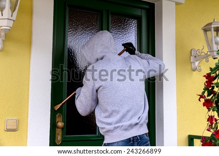 a burglar trying to break a door. - stock photo