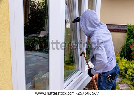 a burglar trying to break in an open window with a crowbar - stock photo