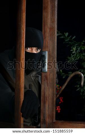 a burglar trying to enter through a window - stock photo