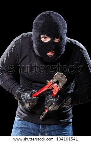 a burglar wearing a balaclava holding huge wire cutters over black background - stock photo