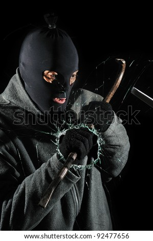 a burglar who broken the glass of a window to enter - stock photo