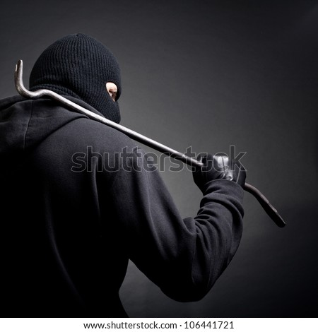 A burglar with a crowbar on the shoulder. View from the back