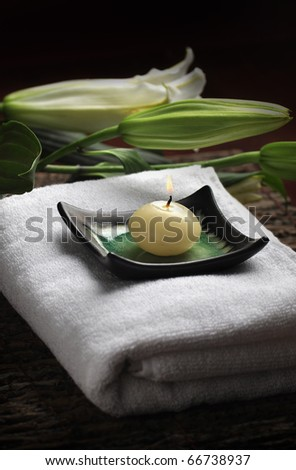 A burning candle on a towel, spa set-up - stock photo