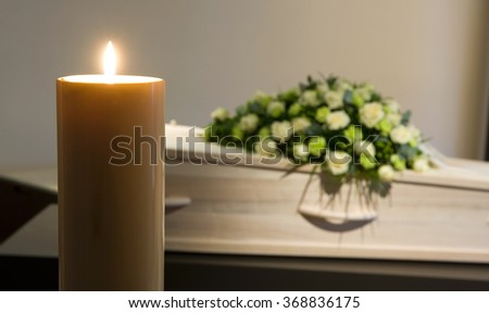 A burning candle with a coffin and a flower arrangement on the background in a mortuary