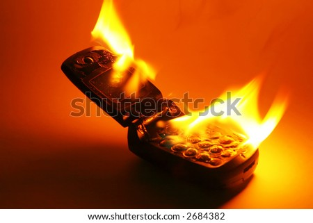 A burning cell phone against a colored background, as an abstract for burning up call time, or eliminating the phone in revenge for its cost. - stock photo