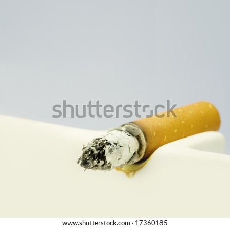 A burning cigarette in a white ashtray - stock photo