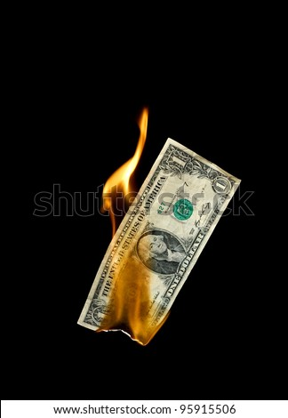 A burning dollar bill symbolizing careless money management and the phrase money to burn - stock photo