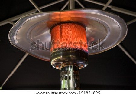 A burning heater under a big parasol  - stock photo