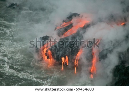 A burning lava flow is seen pouring over rock and into the ocean. Steam can be seen rising from the cold water as the molten lava enters it. - stock photo